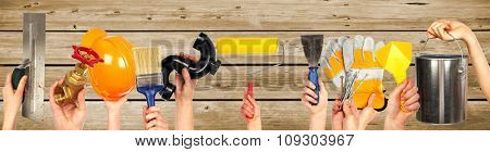 Hands of handyman with tools. House renovation and construction.