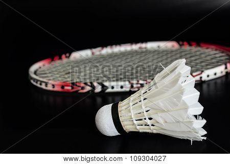 Racket and shuttlecock for badminton sport isolate on black ground.