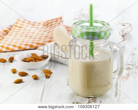 Banana Smoothie On A White Wooden Table.