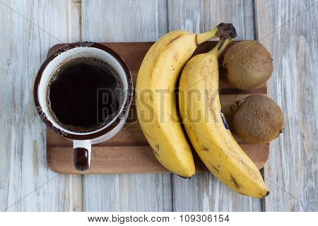 A cup of coffee, bananas and kiwi