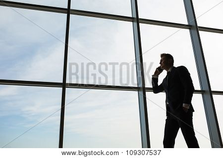 Stylish business man in the background of a large window