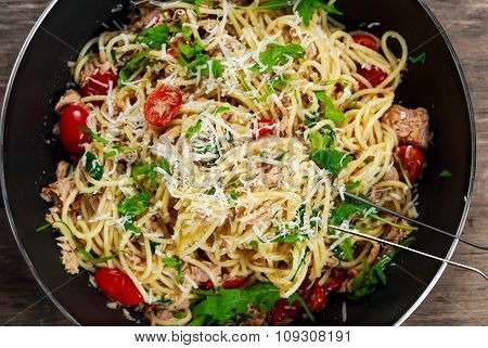 Italian Tuna Pasta Spaghetti In Wok, With Tomato, Chilli, Parmesan And Wild Rocket  Lives. On Old Wo