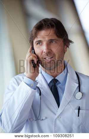 handsome doctor speaking on cellphone at modern hospital indoors