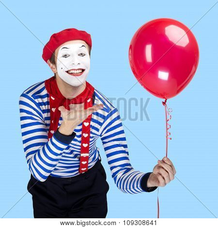 Mime with balloon.Emotional funny actor wearing sailor suit, red beret posing on color blue backgrou