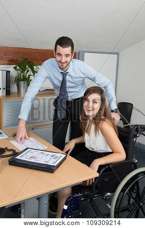 Young Businessman Showing A Document  To A Young Woman In Wheelchair, Assistance And Help Concept
