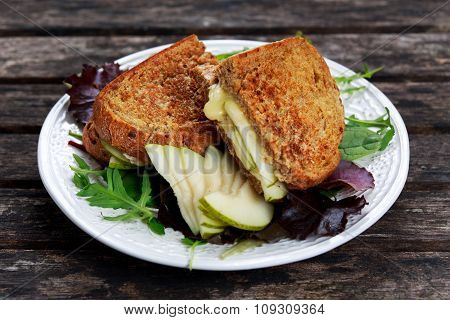Rustic Homemade Bread Grilled Into Sandwich With Pear And Cheese On Old Wooden Table