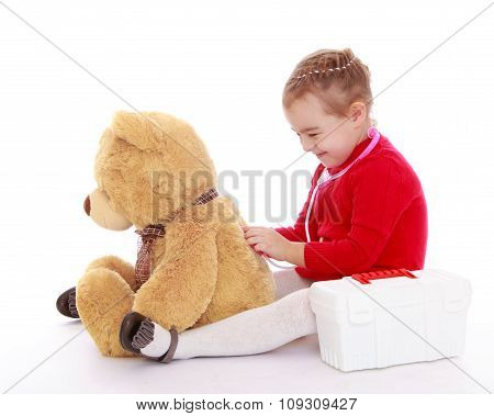 little girl playing with a teddy bear