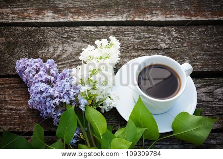 Coffee Cup And Colorful Lilac Flowers On Wooden Background