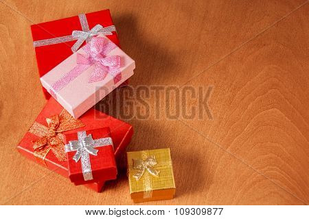 Colored Gift Boxes With Decorative Bows On Wooden Background. Selective Focus