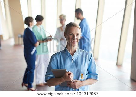 female doctor with tablet computer  standing in front of team  in background, group of medical staff at hospital