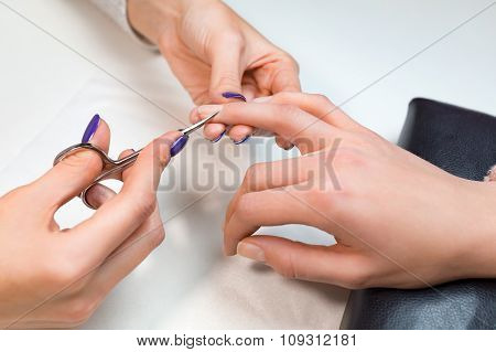 Manicurist cut clients cuticle with nail scissors