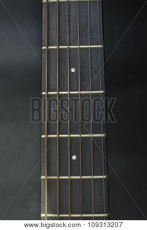Headstock ,fretbord,frets of guitar acoustic on black background.