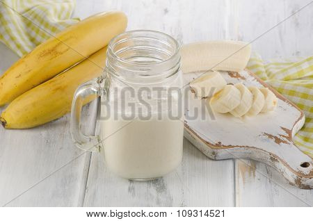 Fresh Made Banana Smoothie On Wooden Background.