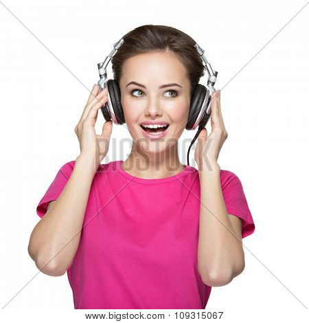 Cheerful young woman listening music with headphones on white background