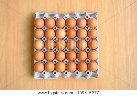 A Dozen Brown Eggs In A Carton On A Wooden Table