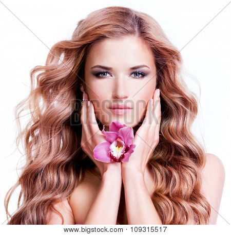 Beautiful young woman with flower near face. Beauty treatment concept. Portrait over white background.