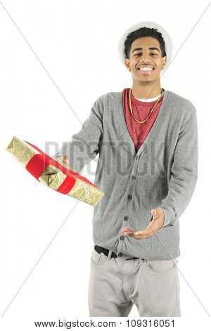 A slim young man happily offering the viewer a Christmas gift, the ring of fluff from his Santa hat seen around his hair.  On a white background.