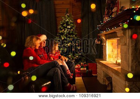 Happy family by a fireplace on Christmastime