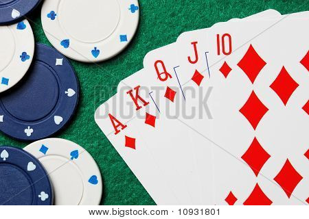 Royal Straight Flush Poker Cards With Gambling Chips On A Green Table Background