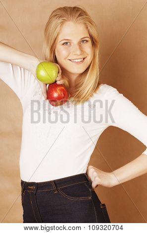 young pretty blond woman choosing between red and green apple smiling