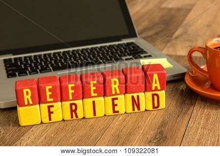 Refer a Friend written on a wooden cube in a office desk