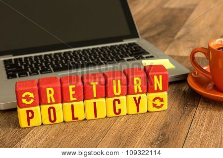 Return Policy written on a wooden cube in a office desk