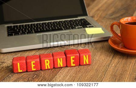 Learn (in German) written on a wooden cube in a office desk