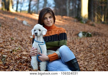 A Girl With Her Dog In Colorful Autumn Forest