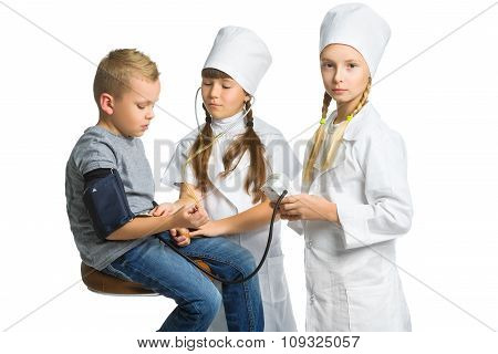 Cute doctor girls measuring blood pressure of a boy patient isolated on white background