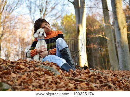 A Girl With Her Dog In Colorful Autumn
