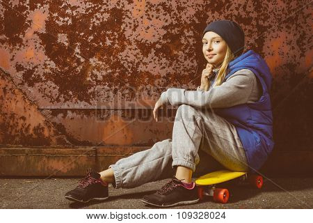 Smiling girl sitting on color plastic penny board or skateboards outdoor