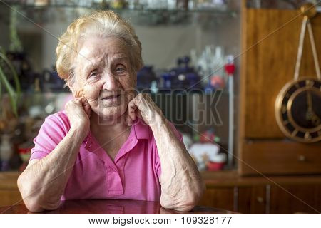 Elderly woman was sitting at the table in room.
