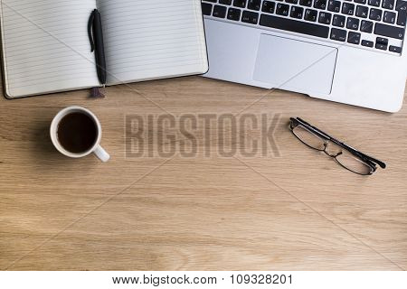 Notepad with pen, keyboard of laptop, glasses and coffee Cup on wooden table top. Top view with space for your text.