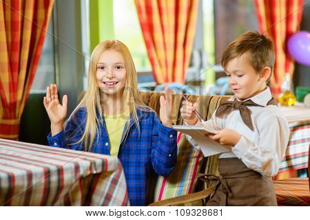 little boy waiter accepts the order in a cafe or restaurant