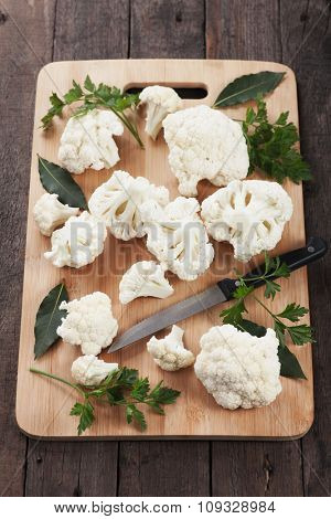 Raw cauliflower on wooden chopping board ready for cooking