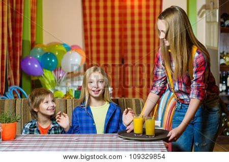 Happy cute smiling girl waiter holding a tray with juice
