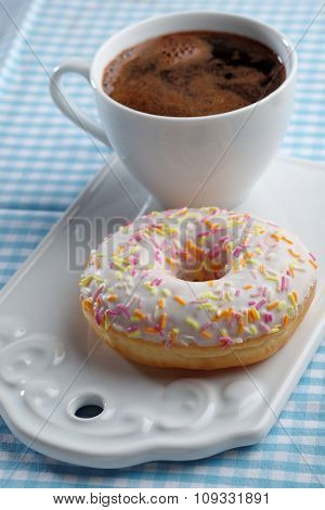Cup of coffee and donut with white frosting and sprinkles on a cutting board