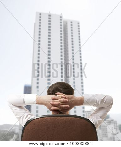 Businessman sitting in office and looking in city