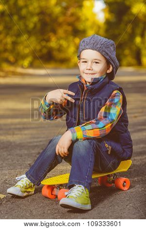Smiling boy sitting on color plastic penny board skateboard at park