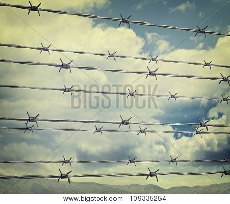 barbed wire background and cloudy sky