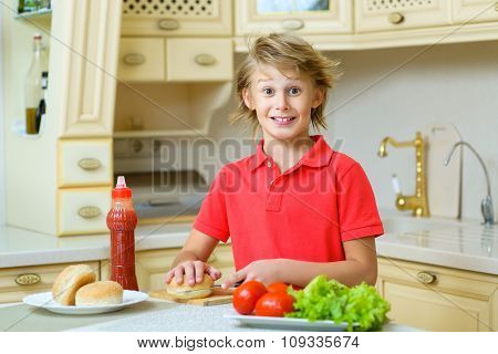 smiling boy holding a hamburger bun and salad in the kitchen
