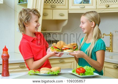 smiling happy boy and girl holding homemade hamburgers or sandwiches