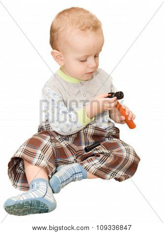 The Little Boy Sits And Considers A Toy Plastic Hammer. The Isolated Figure On A White Background