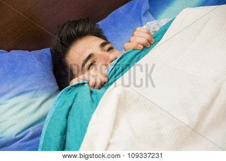 Handsome male model lying alone on his bed sleeping