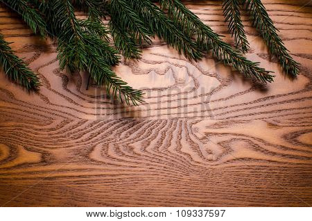 Wooden table background. Spruce branches on a wooden background. Christmas background