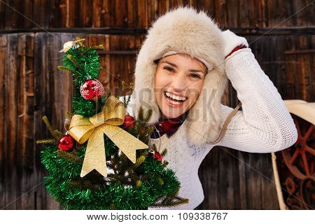 Young Woman With Christmas Tree In The Front Of Rustic Wood Wall