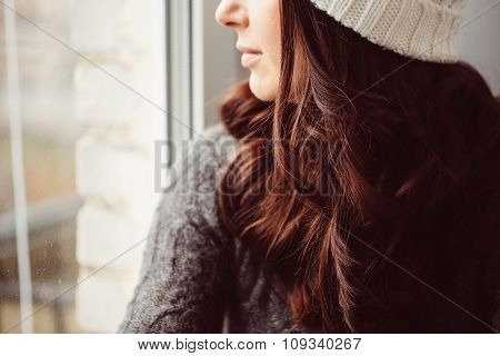 Girl in a cap looks out of the window.
