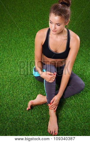 Beautiful young woman relaxing after exerscises on the grass