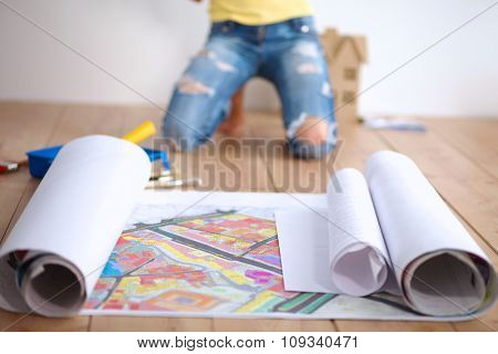 Young woman sitting on the floor and looking at blueprint of new house