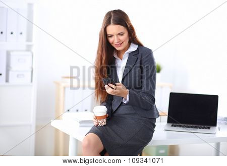 Smiling businesswoman holding disposable cup and smartphone